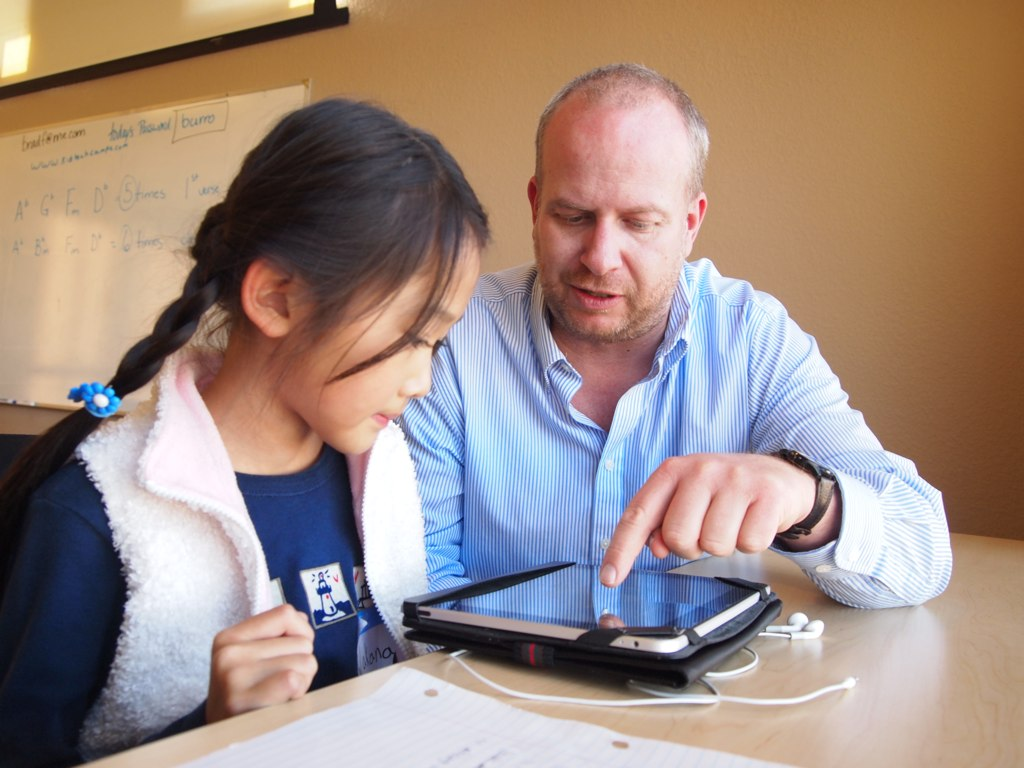 Male teacher directing student's attention to a button on an iPad.